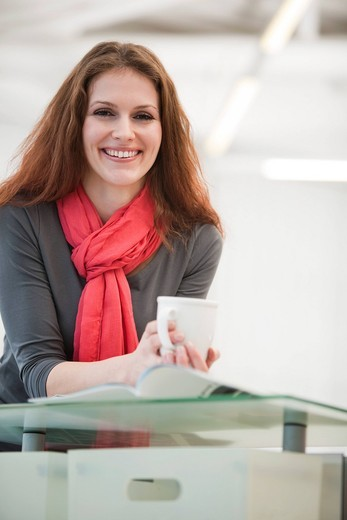 Stock Photo: 1669R-31955 portrait of young businesswoman holding cup