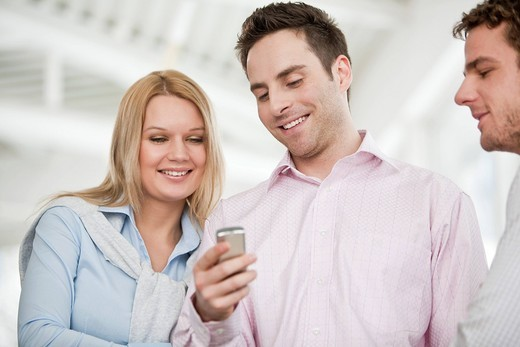young businessman showing text message on mobile phone to colleague : Stock Photo