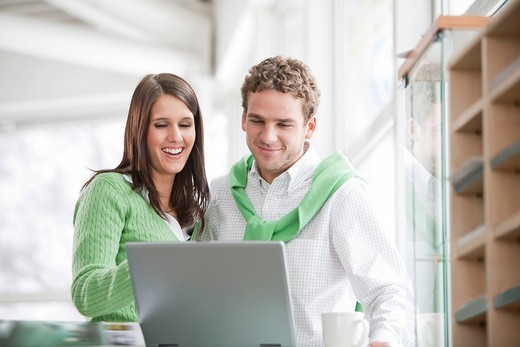 portrait of young businesswoman and male colleague looking at computer : Stock Photo