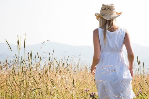 young blond woman standing in field : Stock Photo