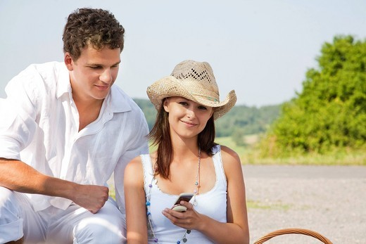 Stock Photo: 1669R-32072 portrait of young couple with mobile phone