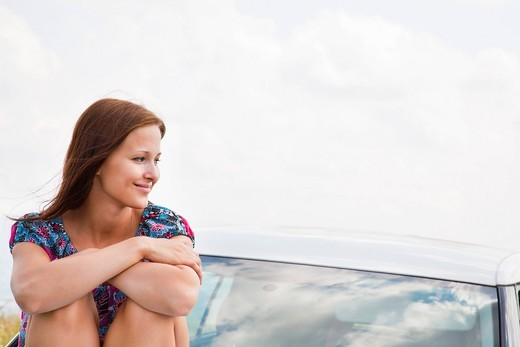 portrait of young woman sitting on bonnet of car : Stock Photo