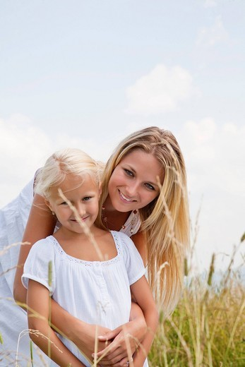 Stock Photo: 1669R-32160 portrait of young woman and daughter in meadow