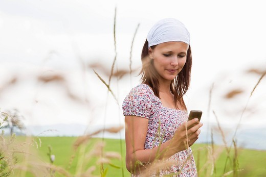 portrait of young woman checking moile phone for text messages : Stock Photo