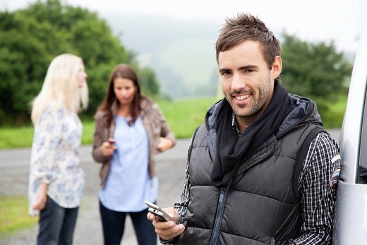 Stock Photo: 1669R-32236 portrait of young man with mobile phone at car