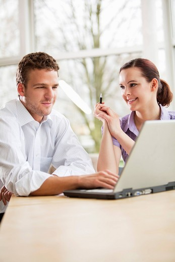 portrait of two business people at table with laptop computer : Stock Photo