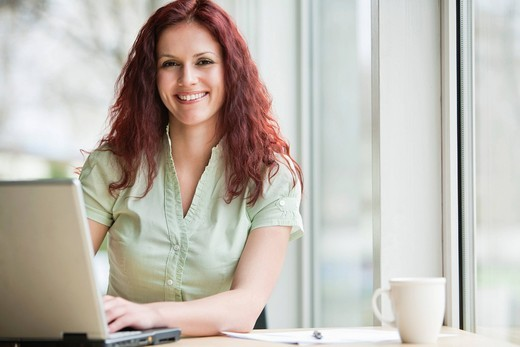 portrait of red haired businesswoman working with laptop computer : Stock Photo