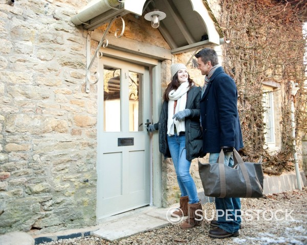 Stock Photo: 1669R-32584 young couple opening door too weekend house in winter