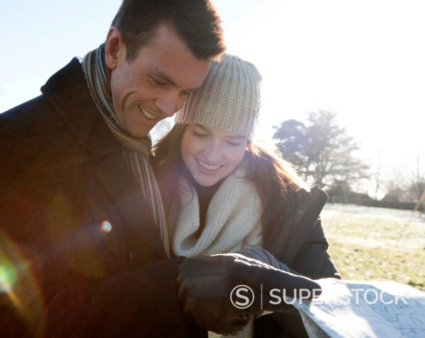 Stock Photo: 1669R-32588 young couple having a walk in winter looking at map