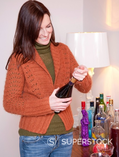 Stock Photo: 1669R-32602 young woman opening bottle of champagne