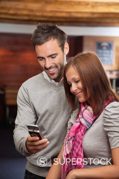 young couple looking at display of mobile phone : Stock Photo