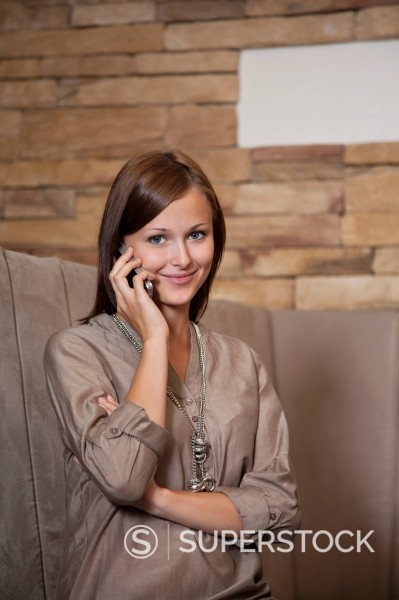 portrait of young woman talking on mobile phone at restaurant : Stock Photo