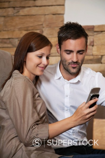 Stock Photo: 1669R-32744 young couple sharing message on mobile phone at restaurant
