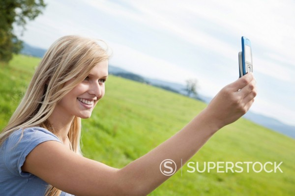 Stock Photo: 1669R-32790 young woman making self_portrait with mobile phone