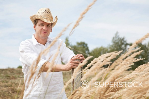 Stock Photo: 1669R-32797 portrait of young man with straw hat in field