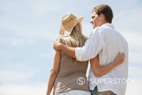 Stock Photo: 1669R-32802 rear view of young couple standing in embrace