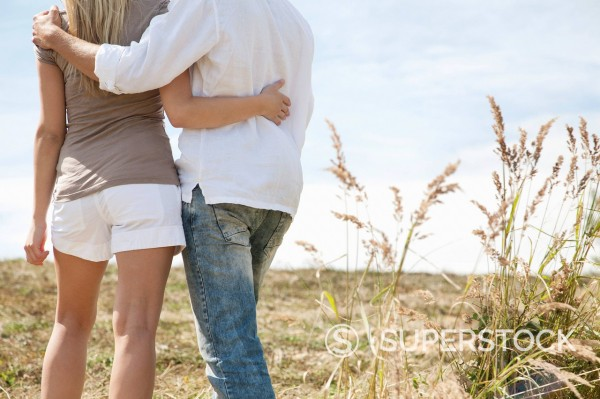 Stock Photo: 1669R-32804 rear view of young couple standing in field