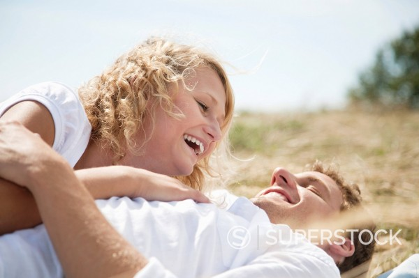 young couple lying in field in summer : Stock Photo