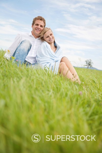 portrait of young couple sitting in grass : Stock Photo