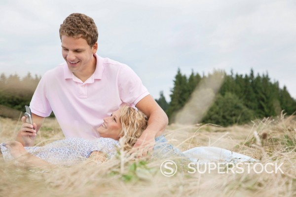 Stock Photo: 1669R-32849 young couple in field man looking at display of mobile phone