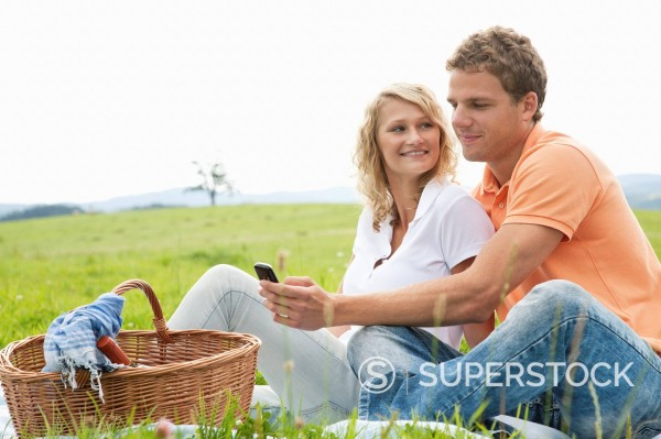 Stock Photo: 1669R-32859 young couple having picnic looking at display of mobile phone