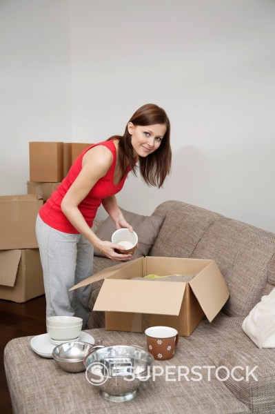 young woman packing crockery in moving box : Stock Photo