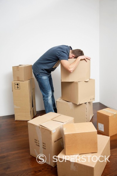 young man searching for something in moving boxes : Stock Photo