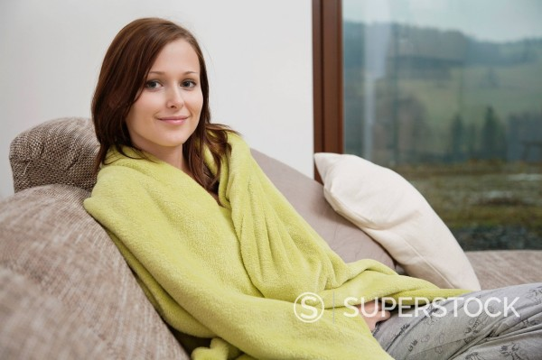 portrait of young woman wrapped in blanket on sofa : Stock Photo