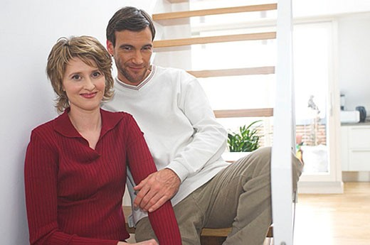 middle aged couple sitting on stairs : Stock Photo