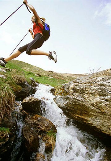Stock Photo: 1669R-3771 woman jumping over brook on nordic walking tour
