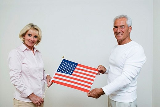 Stock Photo: 1669R-4502 mature man and woman holding flag of the USA