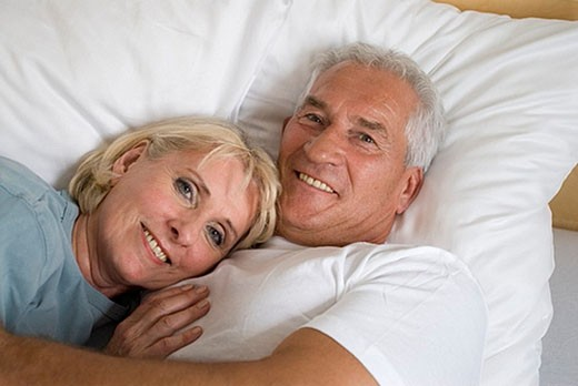 portrait of happy looking mature couple in bed : Stock Photo