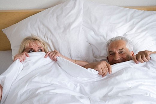 Stock Photo: 1669R-4548 mature couple playfully hiding under the covers
