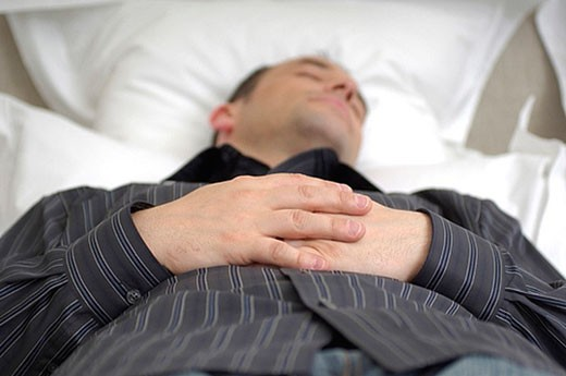 Stock Photo: 1669R-4690 young businessman dozing in bed with folded hands