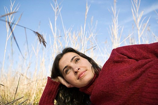 wistfully looking young woman lying in reeds : Stock Photo