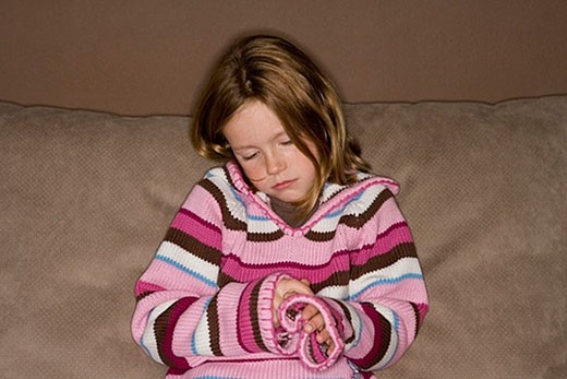 Stock Photo: 1669R-5013 sad little girl sitting by herself on couch