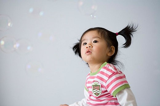 little asian toddler looking at soap bubbles : Stock Photo