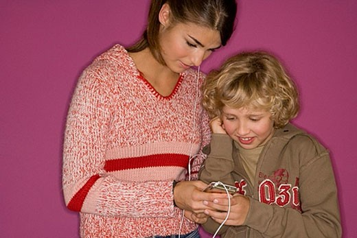 young boy sharing mp3 player with older sister : Stock Photo