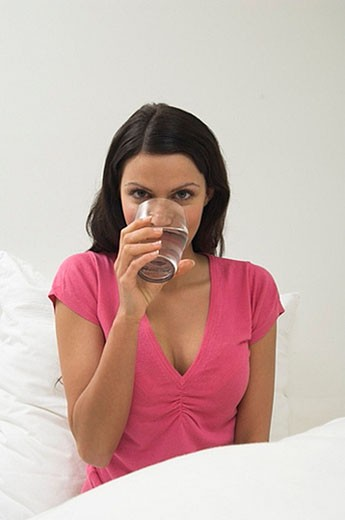portrait of young woman drinking glass of water : Stock Photo