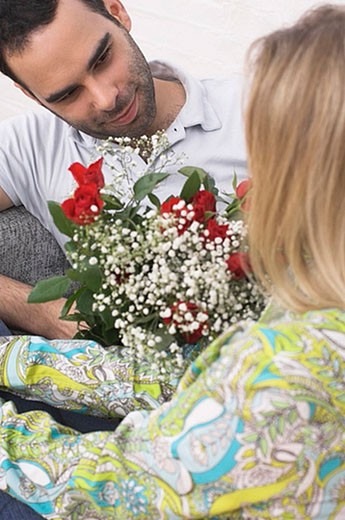 Stock Photo: 1669R-5658 young couple sitting on armchair man giving red roses to woman