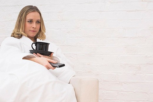 Stock Photo: 1669R-5890 young woman in bathrobe sitting in arm chair holding cup and remote control