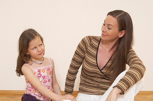 mother and sulking little daughter looking at each other : Stock Photo