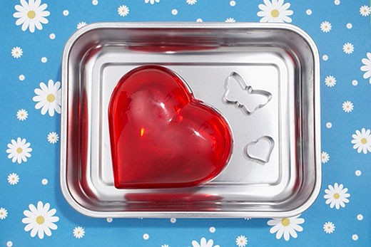 red heart and cookie cutter in shape of butterfly in silver bowl : Stock Photo