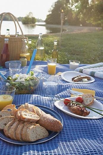 still life of barbecue picnic spread on blanket near lake : Stock Photo