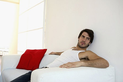 Man sitting on sofa : Stock Photo