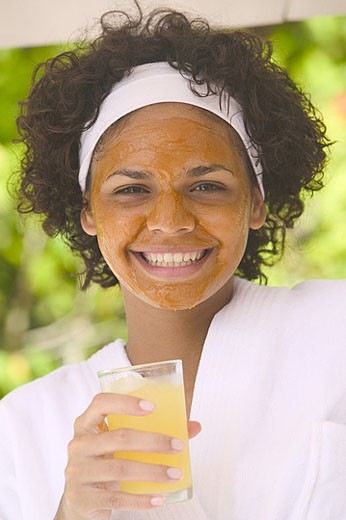 Woman with face mask holding glass with orange juice : Stock Photo