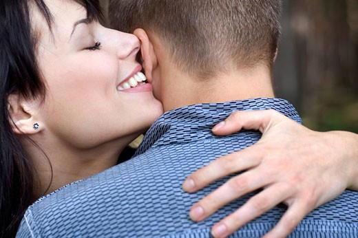 Stock Photo: 1669R-8730 young woman whispering in man´s ear