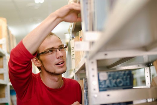 male student with glasses looking for book in school library : Stock Photo