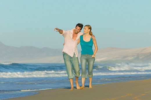 Stock Photo: 1669R-9137 young couple walking along beach together