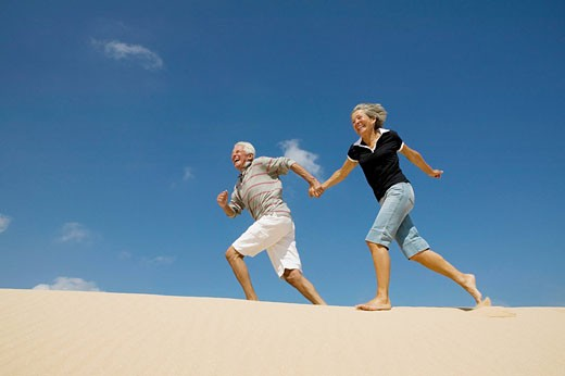 mature couple running on beach hand in hand : Stock Photo